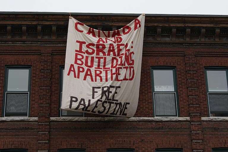 Free Palestine banner hung from a brick building