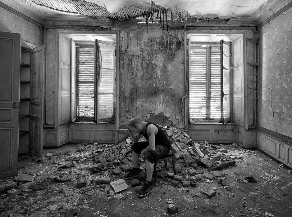 Homeless person in an abandoned building with an open book